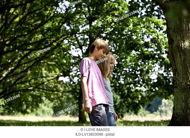 A young boy and girl walking in the park