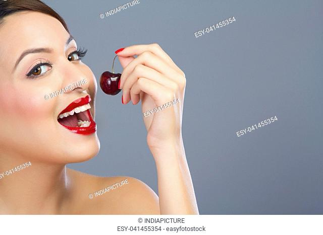 Portrait of a woman about to eat a cherry