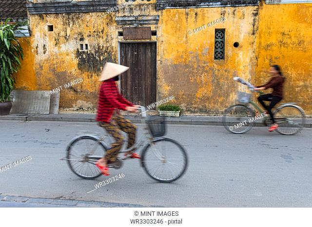 Cyclists on a street in Hoi An, Vietnam