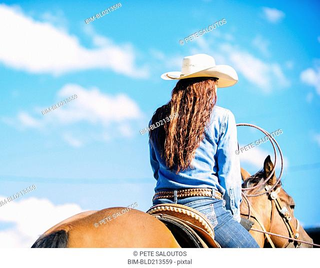 Caucasian cowgirl riding horse in rodeo outdoors