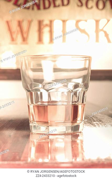 Vintage photograph on a glass tumbler filled with a single serve of blended scotch whisky on pub counter. Luxury liquor