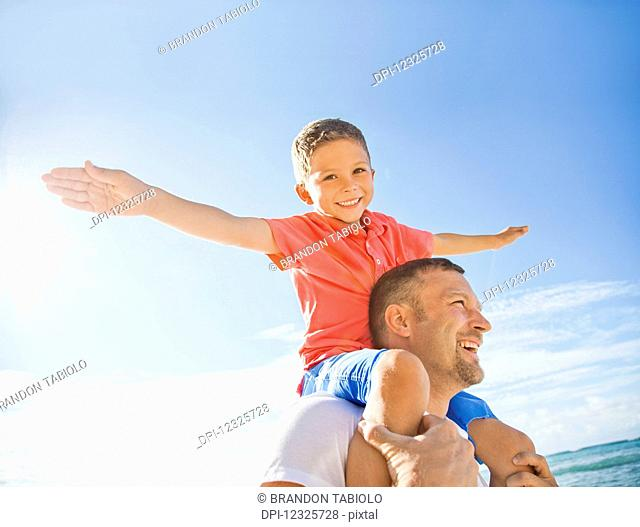 A boy piggybacking on his dad flying like an airplane with his arms; Honolulu, Oahu, Hawaii, United States of America