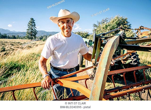 Portrait of Caucasian farmer standing near tractor
