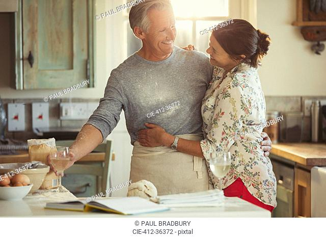 Affectionate mature couple hugging, baking and drinking wine in kitchen