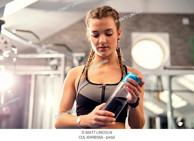 Young woman training, holding water bottle and looking down in gym