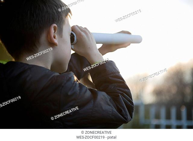 Boy watching something with home-made telescope