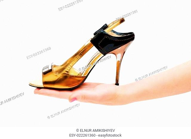 Hand holding woman shoe isolated on white