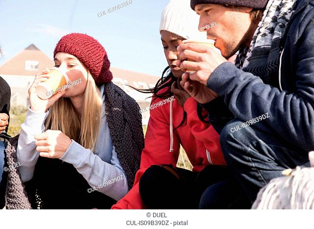 Young adult friends crouching on beach drinking takeaway coffee, Western Cape, South Africa