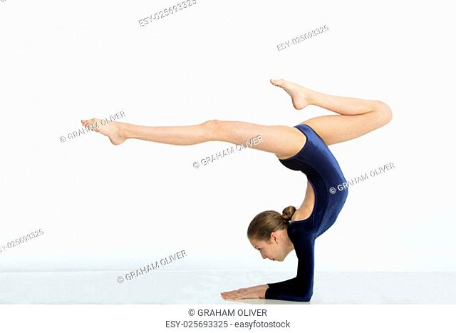 Female gymnast balancing in a pose on her arms against a white background