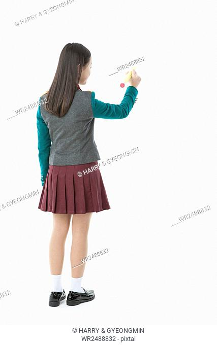 Back of middle school girl standing writing with a pencil