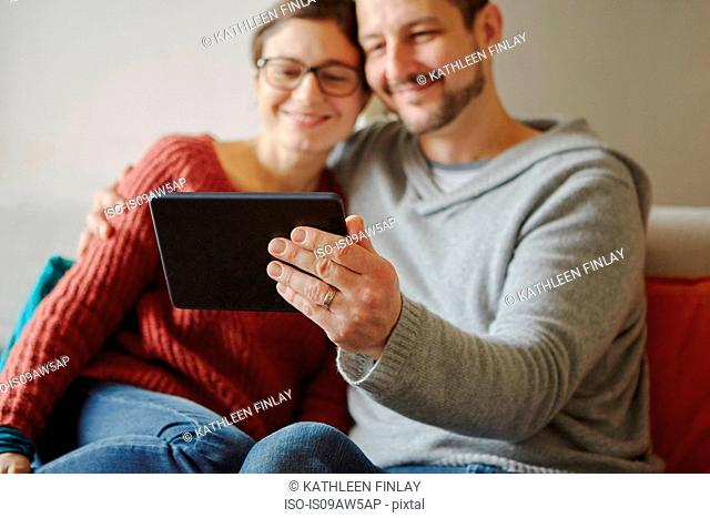 Mid adult couple sitting on sofa taking selfie with digital tablet
