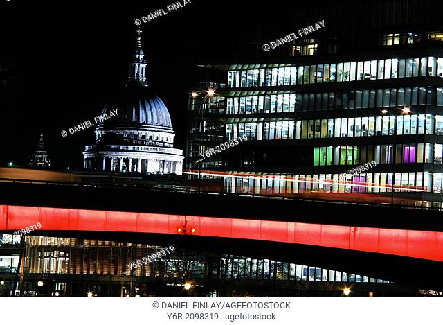 London Bridge at night, with St. Paul's Cathedral and the offices of a major international financial company in the background