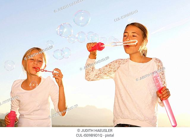 Two young girls, outdoors, blowing bubbles