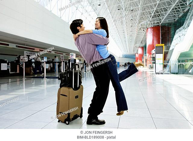 Asian couple hugging in airport