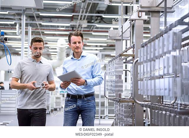Two men with tablet talking about a product in factory shop floor
