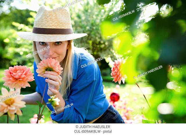 Portrait of mid adult woman smelling garden blooms