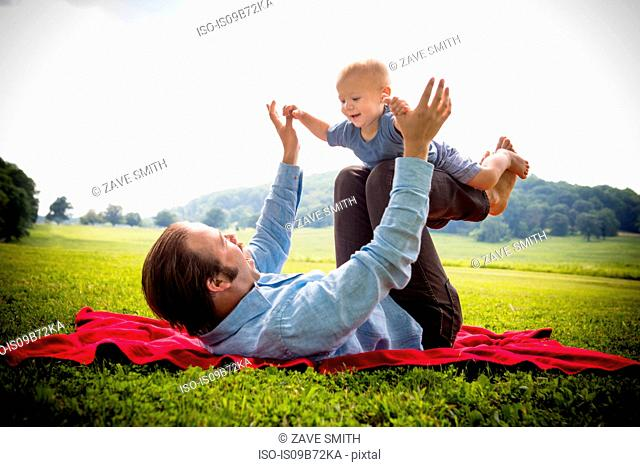 Mid adult man lying on back balancing baby son in rural field