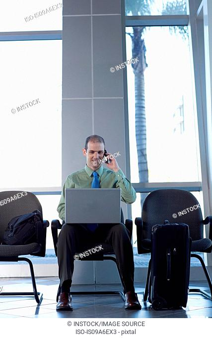 Businessman on cell phone using laptop