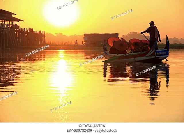 Burmese boatman and buddhist novice sitting in boat, morning sunset in U Bein bridge, Mandalay, Myanmar