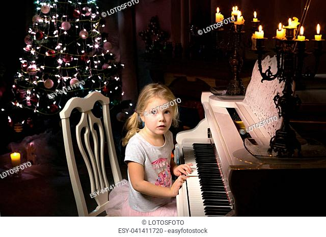 Little girl is playing on a white piano in a dark room by candlelight. Concept Christmas, New Year, holiday, family happiness, childhood
