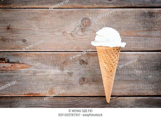 Single vanilla ice cream in a waffle cones over wooden background with copy space