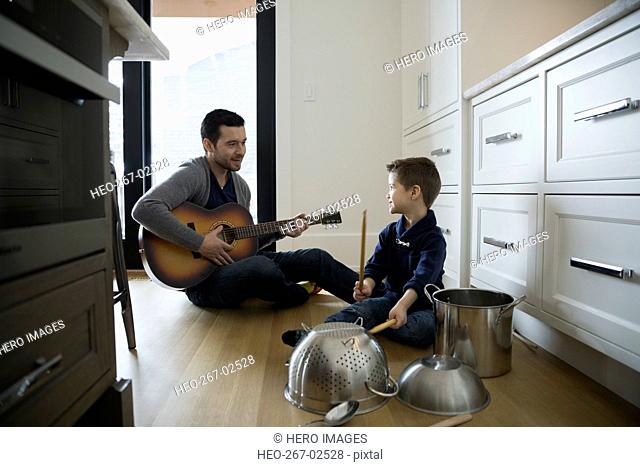 Father playing guitar and son banging kitchen pots