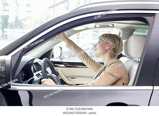 At the car dealer, Woman sitting in new car