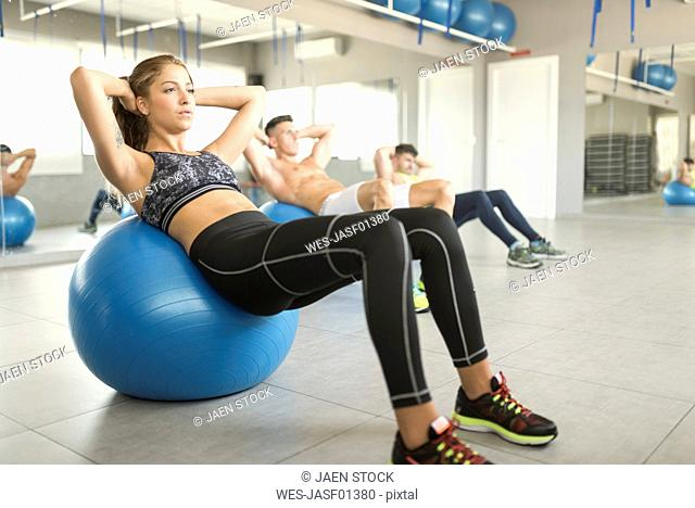 Woman exercising abs on gym ball