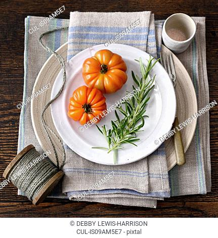 Tomatoes, rosemary, plate, kitchen towel, string