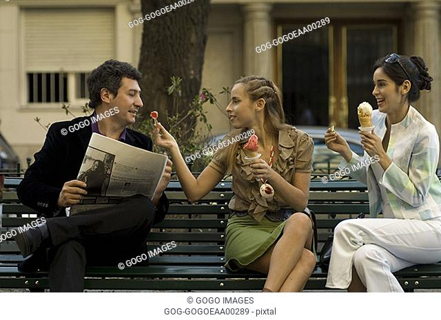 Women sharing ice cream in a park