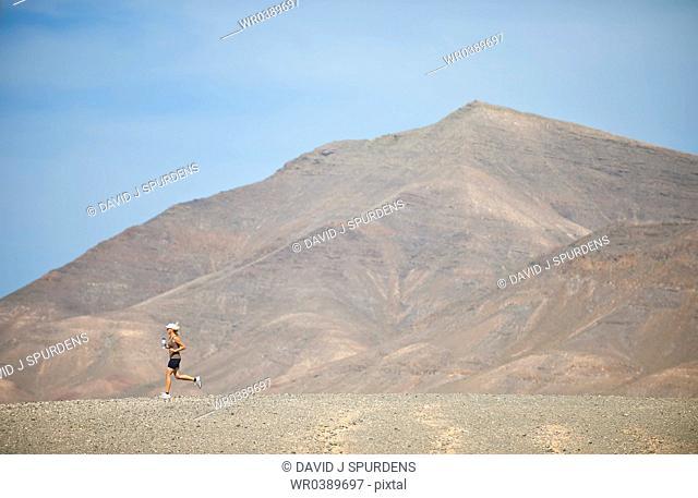 An aultra distance runner jogging through an arid desert with water bottle