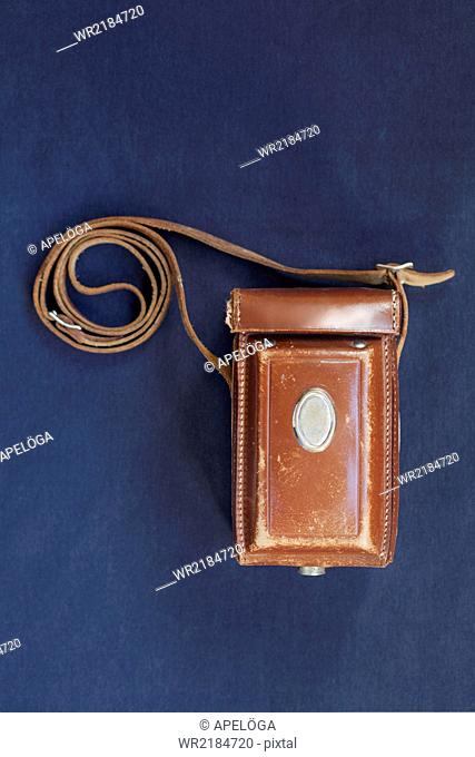 Top view of vintage camera case on blue table