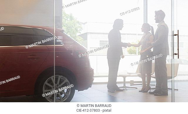 Car salesman shaking hands with couple customers in car dealership showroom