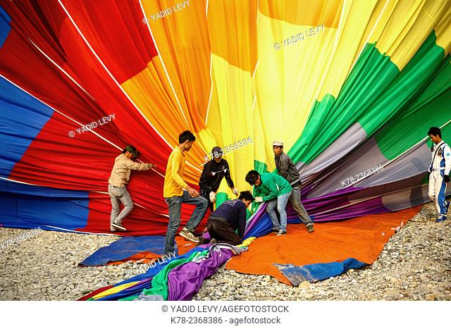 People folding a hot air balloon, Vang Vieng, Laos