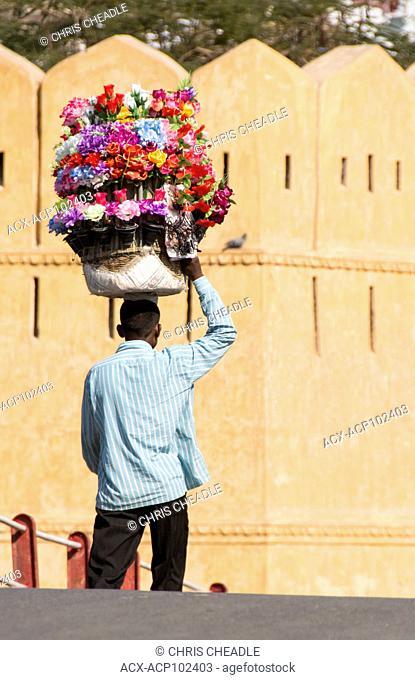 Man carrying artificial flowers over bridge, Udaipur, Rajastan, India