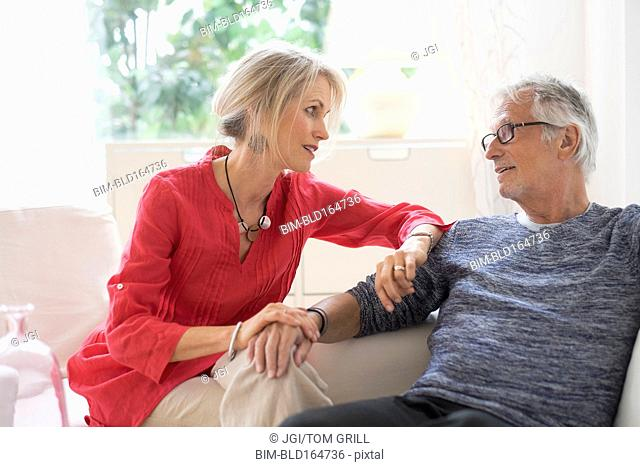 Older Caucasian couple talking in living room