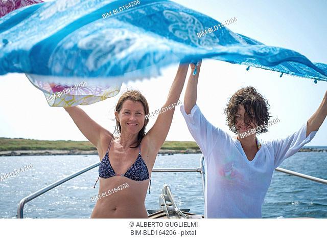 Women spreading blanket on boat in water