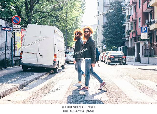 Young male hipster twins with red hair and beards strolling on pedestrian crossing