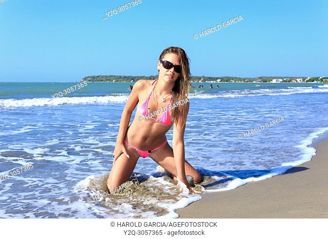 Beautiful woman Posing in a super daring swimwear kneeling and getting wet on the beach of Cartagena, Colombia