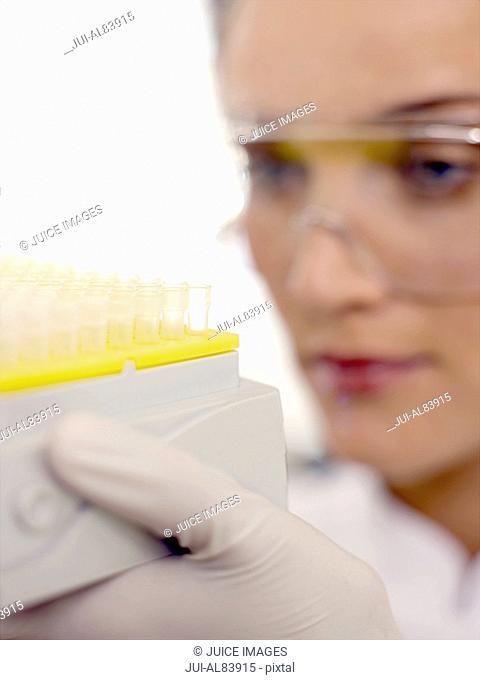 Female scientist examining test tubes in rack