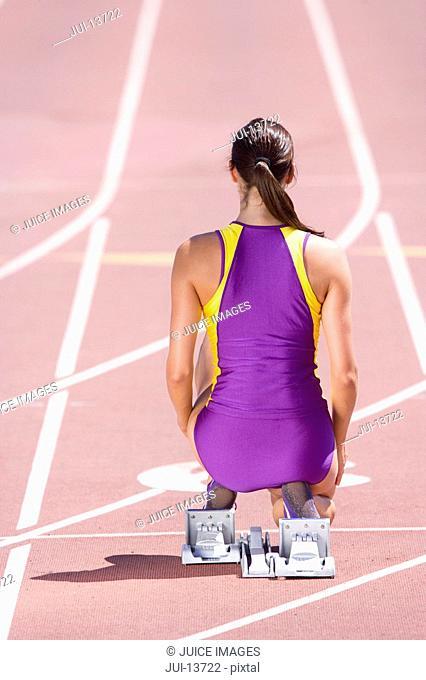 Female runner at starting block kneeling on race track