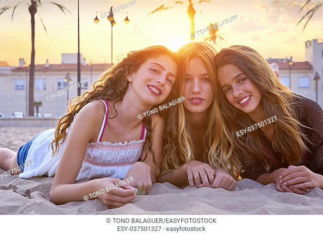 Best friends girls at sunset beach sand smiling happy together