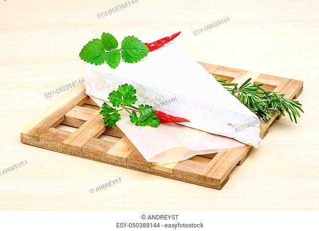 Soft brie cheese with rosemary, thyme on the wood background