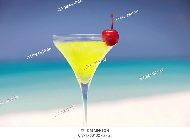 Close up yellow cocktail with cherry in martini glass on sunny tropical beach