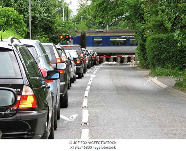 row of cars waiting at rural level crossing at jordanstown northern ireland