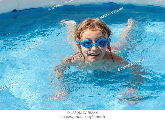 Blonde boy in glasses is swimming in the pool. He is looking at the camera