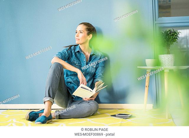 Woman relaxing in her home with potted plants, reading a book