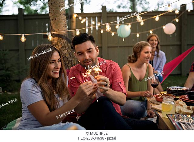 Couple lighting sparklers at backyard dinner party