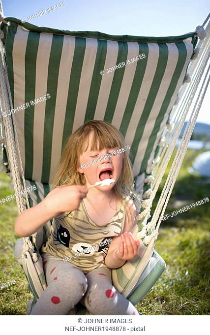 Girl eating ice-cream on hammock, Kiruna, Lapland, Sweden