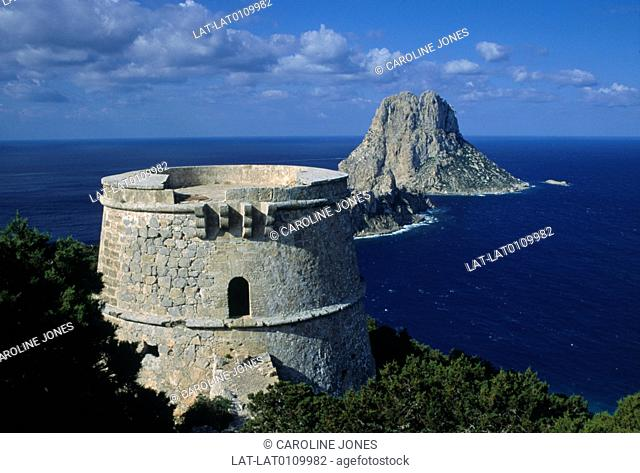 A 18th Century defence tower on the coast,with the Es Vedra rock formation in background